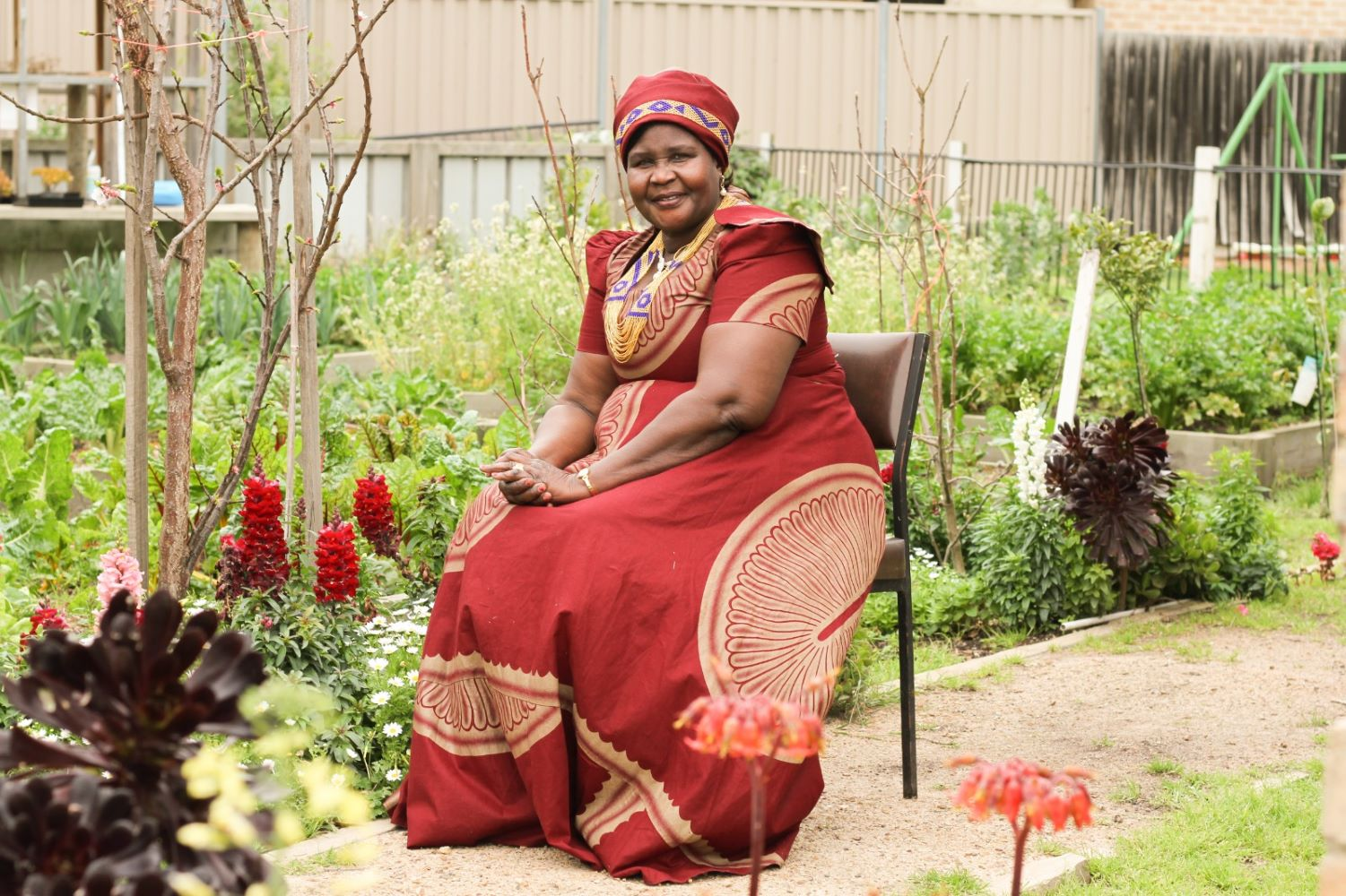 A smiling lady wearing traditional red African dress with head wear siting in a chair in a garden