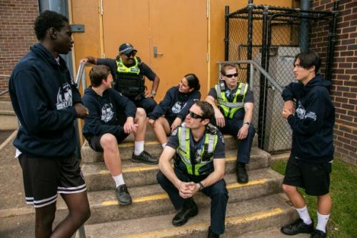 Three police officers and three young people sitting on some steps and chatting