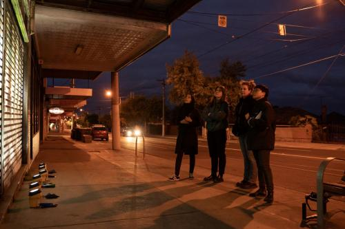 Four women standing on side of the pavement at night observing light treatment