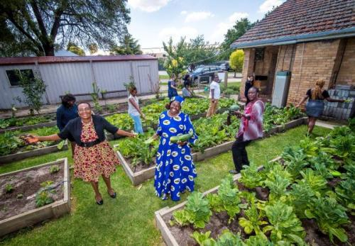 Ten smiling women standing in a vegetable garden at the back of a house