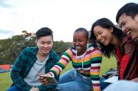 Four young people sitting in a park smiling and looking at a mobile phone together
